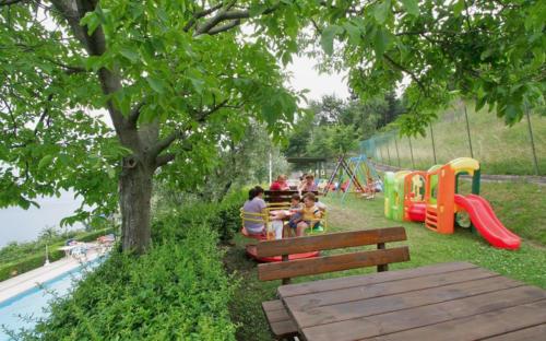 Der Spielplatz unseres Familienhotels Gardasee liegt gleich oberhalb des Swimmingpools